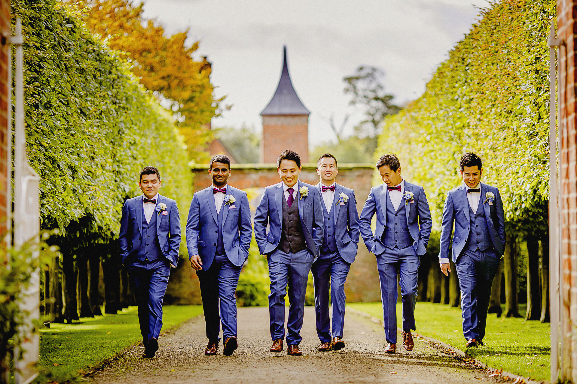 groomsmen arriving at the walled garden, wearing suits, blue, ties, buttonholes