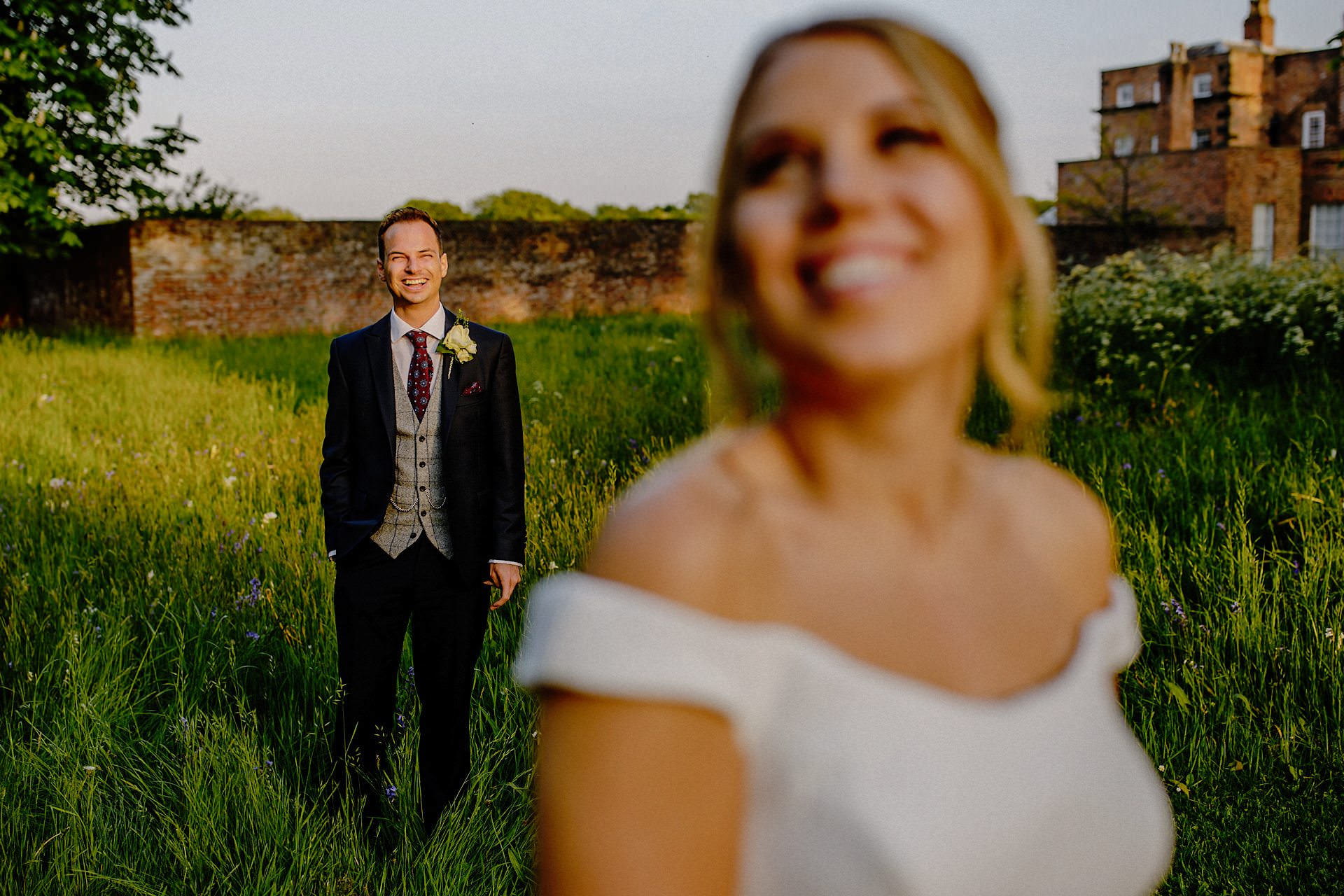 groom laughing, bride out of focus